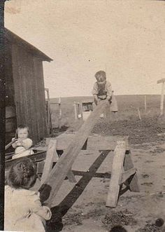 Farm children playing on homemade seesaw