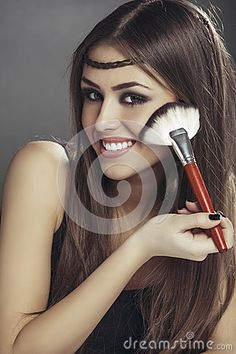 Portrait of a happy young woman applying makeup on her face with a big brush over grey background.