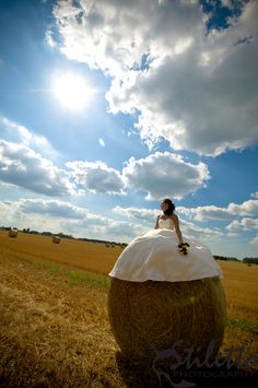 Bride sitting on a round hay bale ~ awesome!