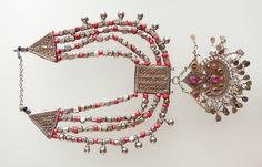 Heavy Yemeni necklace with quite a delicate central pendant.  The different pieces are different grades of silver, ranging from sterling quality to coin silver.  The central pendant with pink glass stones (some missing) looks as if it has been gilded.  The inside of the necklace is 15 1/2 inches around.  The central rectangular pendant with next one attached is  5 3/4 inches tall.  oldbeads.com