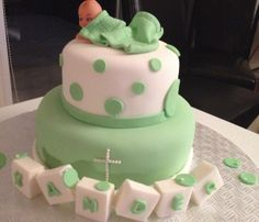 Two tier white and green fondant unique baptism cake, circles and polka dots design with baby under a blanket topper, and name on fondant cubes, the last tier also has white pearl candy cross. Vanilla and cream cheese filling.