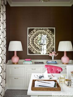 In the wife's office in a Greenwich, Connecticut, house designed by Ashley Whittaker, pink lamps by Christopher Spitzmiller stand out against brown grass cloth by Winfield Thybony.