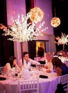 Arboles altos en mesas redondas, formados por ramas blancas de cerezos. Apoyados sobre tapa de espejo y acompañados por velas en vasos cristal Sillas tiffany blancas y mantelería blanca para todas las mesas. By Mercedes Courreges Ambientaciones