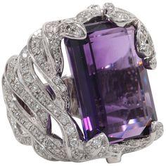 25 carat emerald cut amethyst set in a handmade elaborate diamond mounting. 2.65 carats of round brilliant cut diamonds set in 18k white gold.