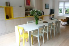 Fitted wall unit and desk running the length of the room uses American white ash veneer and yellow laminate. The funky dining table was designed as a statement piece for centre of the space.