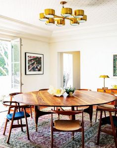 Mid-century modern inspired dinning room with circular wooden table, wood chairs, and gold chandelier
