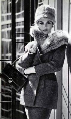 Tweed suit with fur collar by Carven, handbag and gloves by Hermès (Paris 1959).