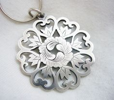 This Argentium Silver pendant is hand pierced and engraved with a beautiful Japanese flower design. The pendant is 33 mm in diameter and comes with a 16 inch sterling silver snake chain.