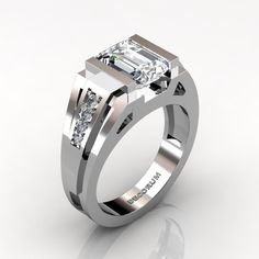 Elegant, luxurious and rich, this mens 14K white gold ring centers a 3.0 carat lab created emerald cut white sapphire, accented with 8 x round 0.015 to 0.020 carat top quality VS-SI G-H white diamonds. All sizes are available. This unique mens ring showcases sophisticated modern design