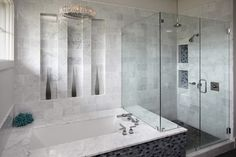 Tiled shower with glass doors. Adjacent marble trimmed tub.