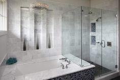 Tiled shower with glass doors. Adjacent marble trimmed tub.