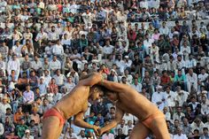 Indian wrestler Biniya from the Jammu Kashmir police, left, fought with Pakistani wrestler Bilal Hussain during an annual traditional wrestling championship at Mathwar Village in Akhnoor, India, Friday. (Agence France-Presse/Getty Images)
