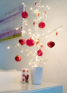 An alternative Christmas tree covered in fairy lights & red decor