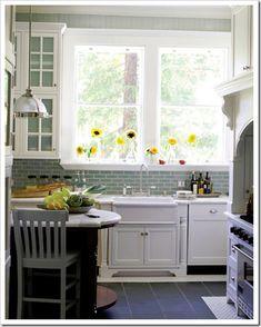 Aqua glass subway tile backsplash, white cabinets, slate floor.