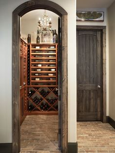 Milestone Custom Homes: Fabulous wine cellar with stained wood wine shelves, chandelier and arched doorway. ...