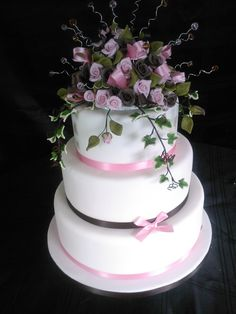 A delicate handmade sugar rose dome in shades of pink and chocolate sit atop this pretty three tier cake.