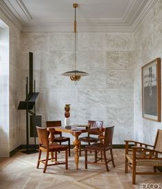 In the living room, an Art Deco games table purchased at an auction in Paris is surrounded by chairs by Kaare Klint. The vintage armchair is by Francis Jourdain, the 1950s pendant light is by Stilnovo; the sculpture in the corner is by Robert Adams, and the painting is by John Forrester.