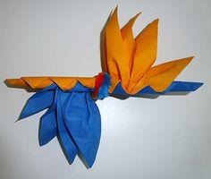 Folding napkin shaped bird of paradise, realize a fle . Small Round Kitchen Table, Origami, Pine Dining Table, Birds Of Paradise Flower, Kitchen Rack, Napkin Folding, Paper Napkins, Communion, Organization Ideas