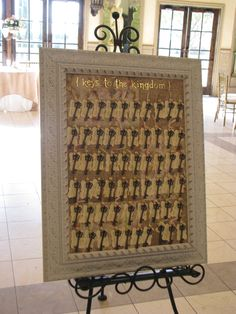 Escort Cards doubled as favors: the skeleton keys are bottle openers! We arranged them in alphabetical order. Wood push pins were purchased from Wal-Mart. Framed cork board was purchased from Hobby Lobby. We stapled vintage-look 12 x12 scrapbook paper (also from Hobby Lobby) to the cork. Shiny gold chipboard stickers from Hobby Lobby.