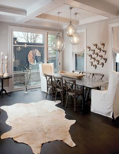 I LOVE this room! Not sure about the tiny antlers but this is great. Demijohn lighting, white cow hide, light walls, chairs and table, old french wood dough bowl... ooooh love it