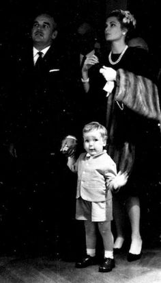 grace:  Making his first official appearance, little Prince Albert, of Monaco, walks between his parents, Prince Rainier and Princess Grace, in the galleries of the Oceanographic Museum. The Monegasque Royal family was attending a ceremony marking the museum's fiftieth anniversary. April 1960.