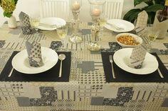 Das Bild zeigt eine große kreative gemusterte Tischdecke mit Tischsets. Die uni Halbleinen Tischsets in Anthrazit setzten einen tollen Kontrast und schmücken den Tisch.