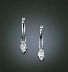 AN ELEGANT PAIR OF DIAMOND EAR PENDANTS    Each set with a marquise-cut diamond weighing 4.34 and 4.63 carats to the articulated diamond-set twin line surmount and old-cut diamond top, mounted in 18k white gold, 5.1 cm long