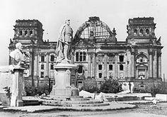 Das kriegsbeschädigte Denkmal des Kaisers Friedrich III. vor dem zerstörten Reichstagsgebäude