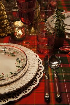 A table set w/Christmas dishes & a tartan tablecloth.  So pretty!