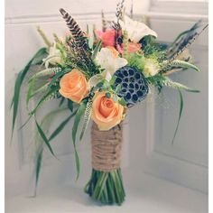 Although most rustic weddings are based around autumnal colours, this beautiful bouquet has lovely orange flowers to brighten up its vibe and the florist has even used feathers to add something different. The wicker string used to tie the flowers together makes it look super rustic and we love the variation of flowers used.
