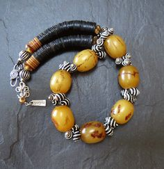 Striking Ethiopian Singed Amber, Zebra Shells and African Vulcanite Necklace by GEMILAJewels  Vulcanite is rubber; it is more common to find vinyl discs on the market today.