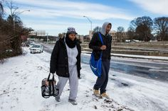 North Atlanta High School student David Hunter and his mother Demetra Dobbins walk up an exit ramp along I-75 North on their way home during the winter storm January 29, 2014 in Atlanta, Georgia