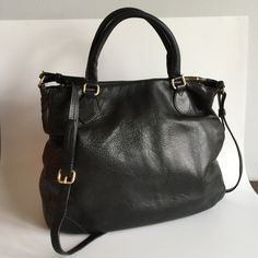 """J. Crew Giant black leather tote cross body So big! Many main compartments that snap and zip shut. The sealant is peeling on a lot of the edging of the leather like shown in picture number 4. Some debris on the interior. Again, many places where the sealant is peeling off. Measures a whopping 16"""" X 13"""" J. Crew Bags"""