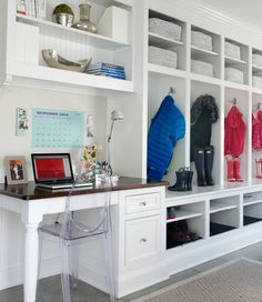 Fantastic mudroom features built in open mudroom lockers fitted with shoe shelves positioned next to  shelves over a built in desk with turned legs paired with a Kartell Victoria Chair.
