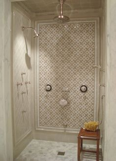 A bells and whistles shower with body sprays and hand shower, a ceiling-mounted showerhead and a wall-mounted head. Plus a bench!