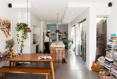 A eclectic kitchen with wooden bench table, stacked books and  white walls.