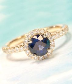 Custom blue sapphire and yellow gold halo engagement ring. Design your own to get the exact ring you want!    Joseph Jewelry | Bellevue | Seattle, WA | Designers of Fine Custom Jewelry