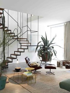 midcentury modern furniture, high ceilings, big house plants and a barely-there staircase... gorgeous!