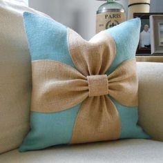 Una paleta de colores relajantes de aqua y de arpillera blanco se combinan para hacer esta cubierta de la almohadilla de arco hermoso. El lado de fondo y la parte posterior de esta cubierta se hace con una arpillera sultana aqua/azul. La porción del arco se hace con de arpillera