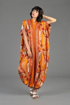 1960s/70s silk jumpsuit. Bright orange psychedelic ethnic-inspired floral + paisley pattern. Caftan shape with elastic cuffs at ankles.