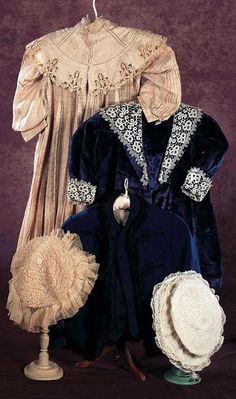 Circa 1890 blue velvet coat with pleated front, padded flannel lining, silk collar lining, Belgian cotton lace collar, along with white cotton cap with wide brim, lace and embroidery details. Via Theriault's.