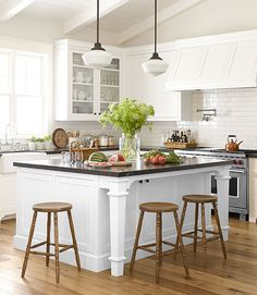 The spindle-leg stools that surround the kitchen island (painted Right White by Restoration Hardware) in this California home are hand-me-downs from the homeowner's parents.   - CountryLiving.com