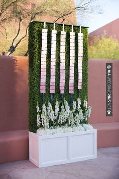 "Escort card display, ombre escort cards on navy ribbon. The cards started cream and faded into a blush pink. The boxwood hedge sat in a flower box where white snap dragons ""grew"" up towards the escort cards hanging above."
