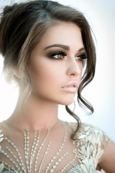 An angelic look by Fady Kataya - Visit the website to view, & get inspiration, from more of the beautiful pictures like this one | A lovely style makeup & look. Frosty nude lips, brown & gold smokey eye, radiant flawless skin, side part in a loose up-do, curls framing the face, exquisite looking bridal wear, an elegant look.