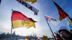 Deutschland-Fahnen und Pegida-Fahnen wehen im Wind vor blauem Himmel, am unteren Bildrand ist die Dresdener Altstadtkulissezu sehen und Menschen, die demonstrieren. (imago stock&people)