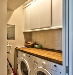 A butcher block countertop placed over the washer dryer maximizes the work  area in a small laundry room.
