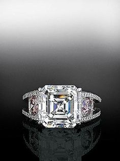 Asscher cut diamond flanked by fancy pink diamonds in a micro pave split shank mounting.