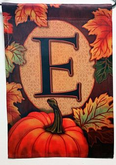 Fall Pumpkin Monogram E Decorative Garden Flag by Carson. $7.99. Specially treated to be fade and weather resistant. Monogrammed and readable from both sides. Constructed of high-quality nylon fabric. This fall, welcome everyone to the 'E' family homestead with this autumn themed monogram decorative garden flag.  Beautifully decorated in fall colors, this decorative flag features falling leaves and a bright pumpkin bordering your family 'E' monogram.  Readable from both sides...