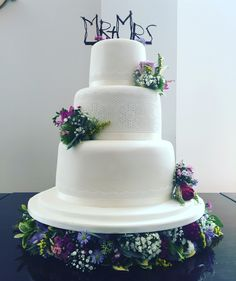 Wedding cake flowers on each tier and around the base. Gypsophilia, sweet William, freesia, roses, nigella, giving the wild flower look