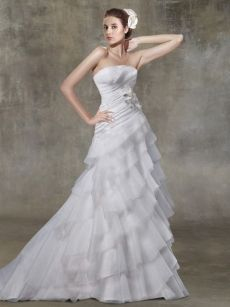 Strapless pleated bodice embellished with flower. Organza gown with pleated tier asymmetric skirt. Zipper back. Chapel train. Fabric: Organza.
